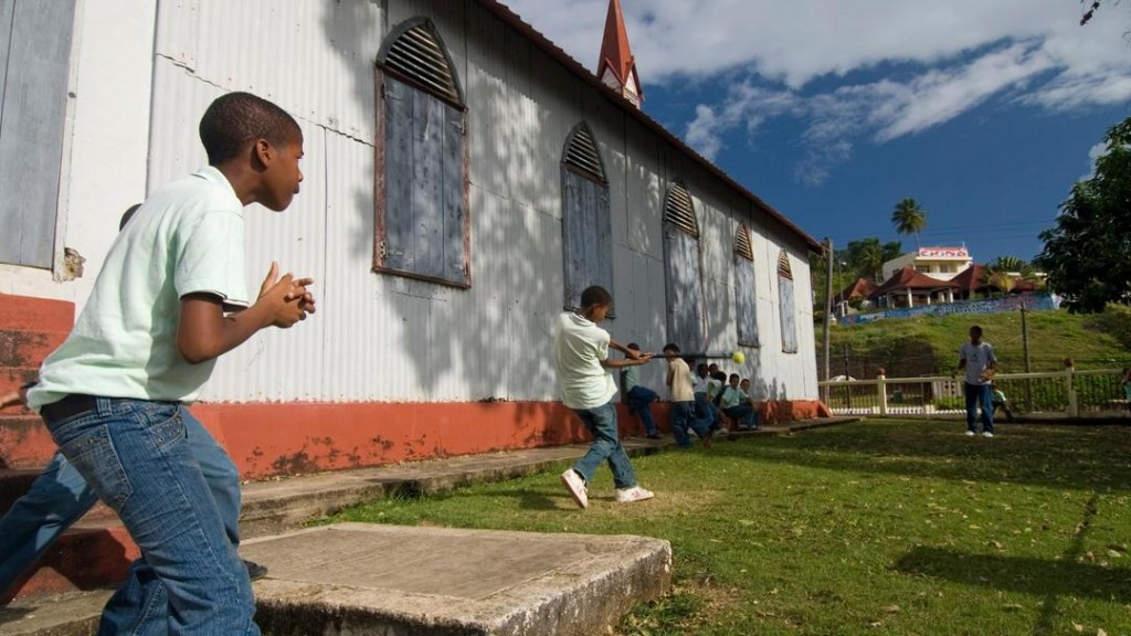 Boys playing baseball in small grounds of old church in Samana town.