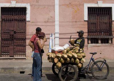 Coconut salesman on his bicycle in front of colonial building, Santo Domingo.