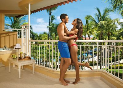 Couple on the balcony of the Honeymoon Suite with Jacuzzi at the all inclusive hotel Dreams Punta Cana in the Dominican Republic