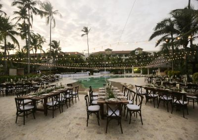 Rustic poolside wedding reception under palmtrees at the all inclusive hotel Now Larimar in Punta Cana, Dominican Republic